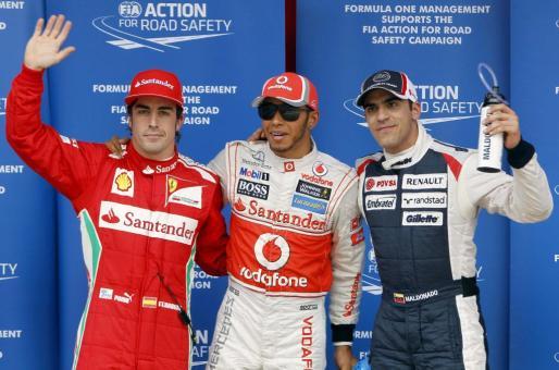 Los pilotos, el británico Lewis Hamilton (c), Fernando Alonso (i) y el venezolano Pastor Maldonado posan tras conseguir los tres mejores tiempos en la sesión de clasificación del Gran Premio de España.