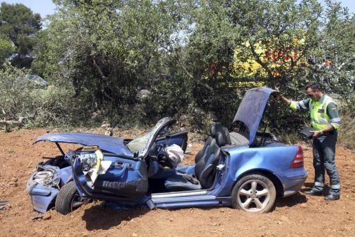Un guardia civil, junto al vehículo accidentado en la vía Llucmajor-Campos, una de las más peligrosas de Mallorca.