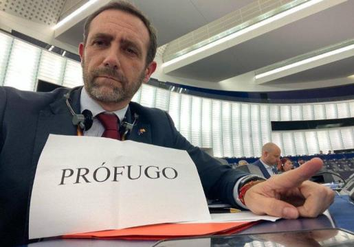 El expresidente balear sostuvo un cartel de protesta durante la intervención de Puigdemont ante los eurodiputados.