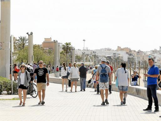 Un grupo de viajeros pasea por la Platja de Palma en temporada baja.