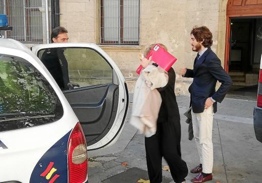 La mujer, acompañada por su abogado Javier Llop, ayer antes de entrar en el coche policial.