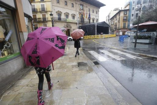 Varias personas caminan bajo la lluvia en Cort, donde hay instalado uno de los escenarios de la Revetla.