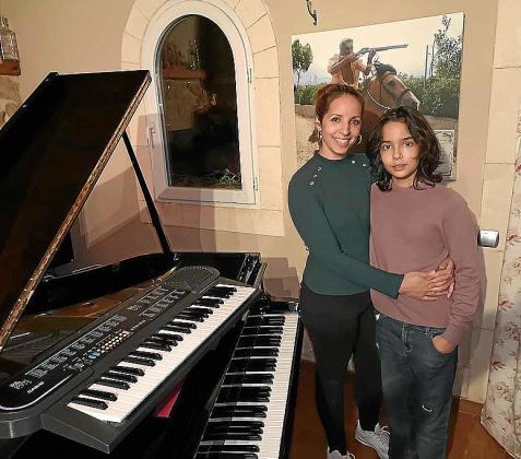 Antón, con su madre, y el teclado que ésta encontró en un contenedor.