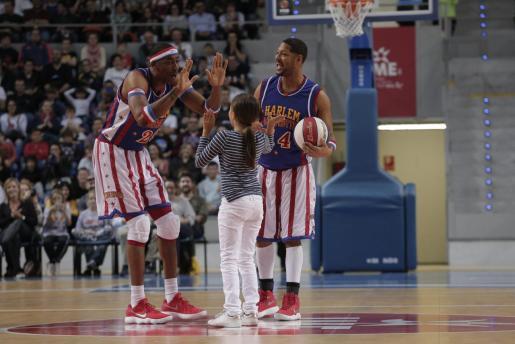 Dos jugadores de los Harlem Globetrotters bromean con una joven aficionada en el centro de la pista.