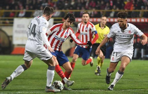 El centrocampista portugués del Atlético de Madrid, Joao Felix intenta llevarse el balón ante los jugadores de la Cultural Leonesa, Julen Castañeda y Virgil Théresin, durante el encuentro correspondiente a los dieciseisavos de final de la Copa del Rey.