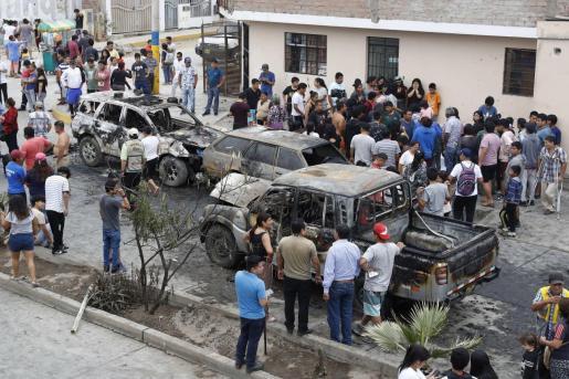 Decenas de personas observan los daños en varios vehículos tras la explosión de un camión en el distrito de Villa El Salvador, al sur de Lima (Perú).