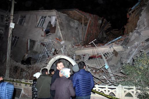 Un grupo de personas ante un edificio derruido por el seísmo.