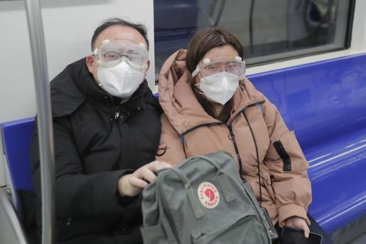 Dos personas portan máscaras en el metro de Beijing.