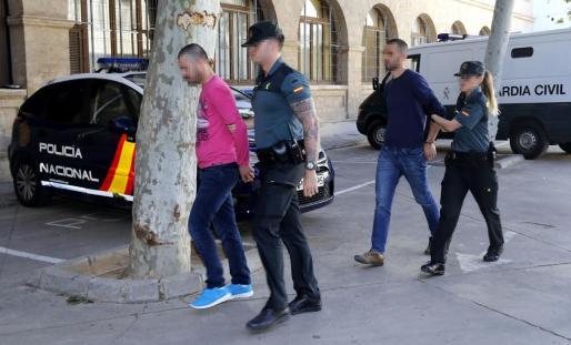 Dos de los detenidos, en los juzgados de Palma, en abril de 2019. A la derecha, uno de los delincuentes mueve una cámara de seguridad de un chalet.