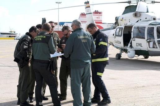 Personal de la Guardia Civil tras el aterrizaje de un helicóptero de la Guardia Civil en el puerto de Ibiza, que se ha incorporado a los operativos en el dispositivo de búsqueda de los dos desaparecidos en Ibiza a causa de la borrasca Gloria.