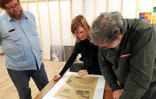 Pedro G. Romero, Marina Planas y Joan Fontcuberta observan un número antiguo del diario 'Baleares' del archivo Casa Planas.