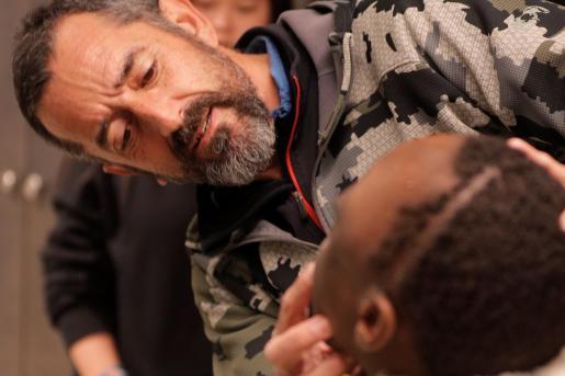 El cirujano Pedro Cavadas observa la cara de Emmanuelle, el niño congoleño de 10 años al que ha extirpado un tumor cráneo facial no maligno que formaba una masa mas grande que su cabeza.