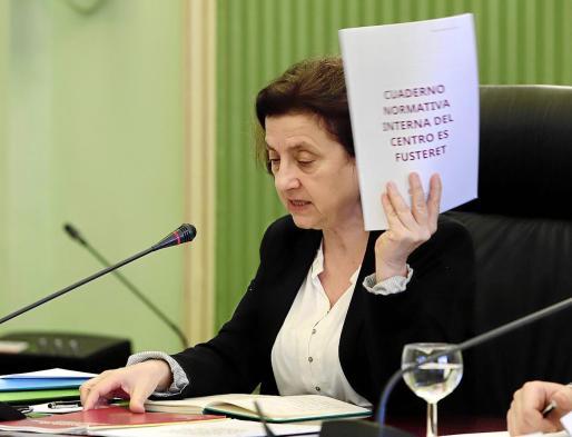 La consellera Fina Santiago muestra la normativa interna del funcionamiento de Es Pinaret durante su comparecencia en la sala verde del Parlament.