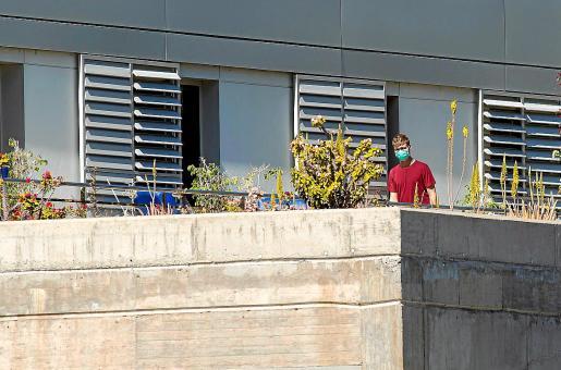 Un joven turista con mascarilla, en el balcón de un hospital de La Gomera.