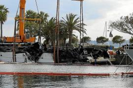 Dos grúas reflotan el yate incendiado en el Puerto Portals