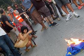 Un centenar de personas 'indignadas' quema una bandera de la UE ante la sede del PP