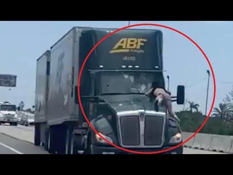 Un camión circula a toda velocidad con un hombre sobre el capó