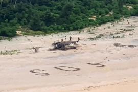 Tres náufragos salvan su vida gracias a un gran SOS escrito en la arena