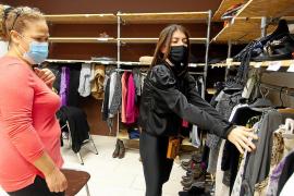 Una de las alumnas mira ropa, ayudada por una de las voluntarias de Cáritas