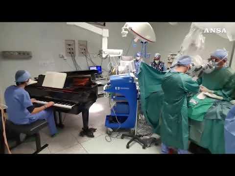 Operan a un niño en Italia con un doctor tocando el piano en el quirófano
