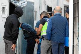 Agentes de la Policía Nacional esposan a uno de los detenidos en la calle Alt