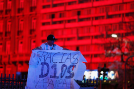 A fan holds a banner as people gather to mourn the death of Argentine soccer great Diego Maradona at the Obelisk of Buenos Aires