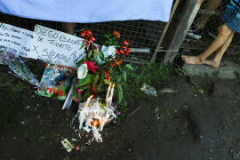 A child stands next to candles and messages left for soccer legend Diego Maradona outside the house where he spent his childhood, in the low income neighbourhood Villa Fiorito, on the outskirts of Buenos Aires