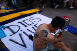 A fan lights a tribute as they gather to mourn the death of Argentine soccer great Diego Maradona at the Obelisk of Buenos Aires