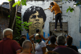 People gather outside the house were soccer legend Maradona spent his childhood as an artist paints a mural of Maradona on the outskirts of Buenos Aires