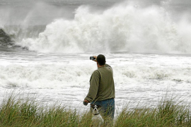 A man with a small dog takes a photo of the storm waves from Hurricane Sandy in Ocean City, New Jersey