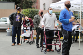 People queue to receive coronavirus disease (COVID-19) vaccinations at the LA Mission homeless shelter on Skid Row, in Los Angeles