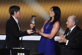 FIFA President Blatter applauds as Solo of U.S. presents FIFA Women's World Player of the Year 2012 trophy to her compatriot Wam
