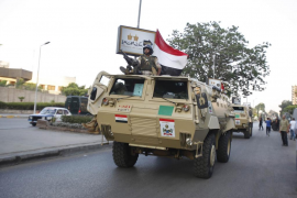 Soldiers in military vehicles proceed towards the presidential palace in Cairo
