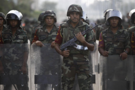 Army soldiers take their positions in front of protesters who are against Egyptian President Mohamed Mursi, near the Republican