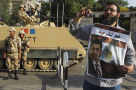 Army soldiers stand guard near a supporter of ousted President Mohamed Mursi at Cairo University