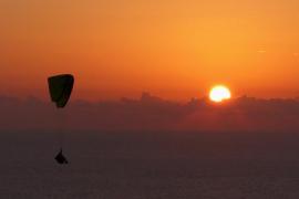 ultraligero volando en la puesta de sol