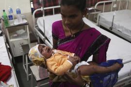 Una mujer sostiene a un bebé que sobrevivió al corrimiento