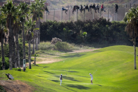 Una imagen de inmigrantes subidos a la valla de Melilla junto a un campo de golf, estrella en las redes sociales