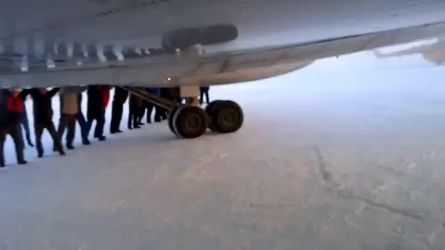 Unos pasajeros empujan su avión en un aeropuerto siberiano para poder despegar