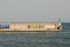 El artista Gustavo trabaja en el segundo mural para el muelle de Cala Rajada