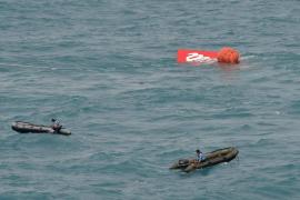 Logran sacar a la superficie la cola del avión de AirAsia sin las cajas negras