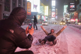Valentin Borriello, from Paris, France, has his photograph made by a friend while lying on 7th Ave during snow storm in Times Sq