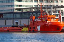 Un remolcador navega hacia el ferry incendiado