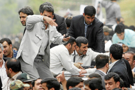 Bodyguards react after the sound of an explosion behind the entourage of Iranian President Ahmadinejad as he is welcomed to Hama