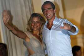 Prince Nikolaos and Tatiana Blatnik wave to the media on the island of Spetses