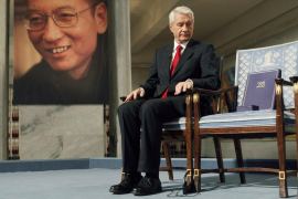 Chairman of Norwegian Nobel Committee Jagland looks down at Nobel certificate and medal on empty chair where Liu would have sat,