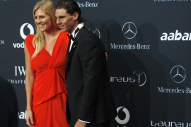 Tennis player Nadal poses with Australian surfing champion Gilmore as they arrive on the red carpet in Abu Dhabi