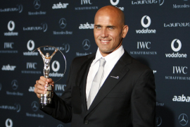Ten-time world surfing champion Slater poses with his third trophy during the Laureus World Sports Awards in Abu Dhabi