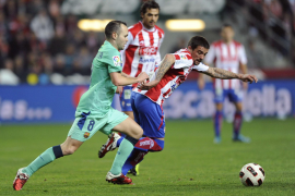 Barcelona's Iniesta fights for the ball with Sporting Gijon's Novo during their Spanish First Division soccer match in Gijon