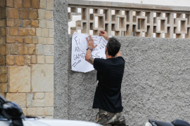 Un vecino cuelga una pancarta en apoyo al expiloto (Fotos: Arguiñe Escandón).